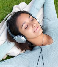Woman lying on grass listening to music